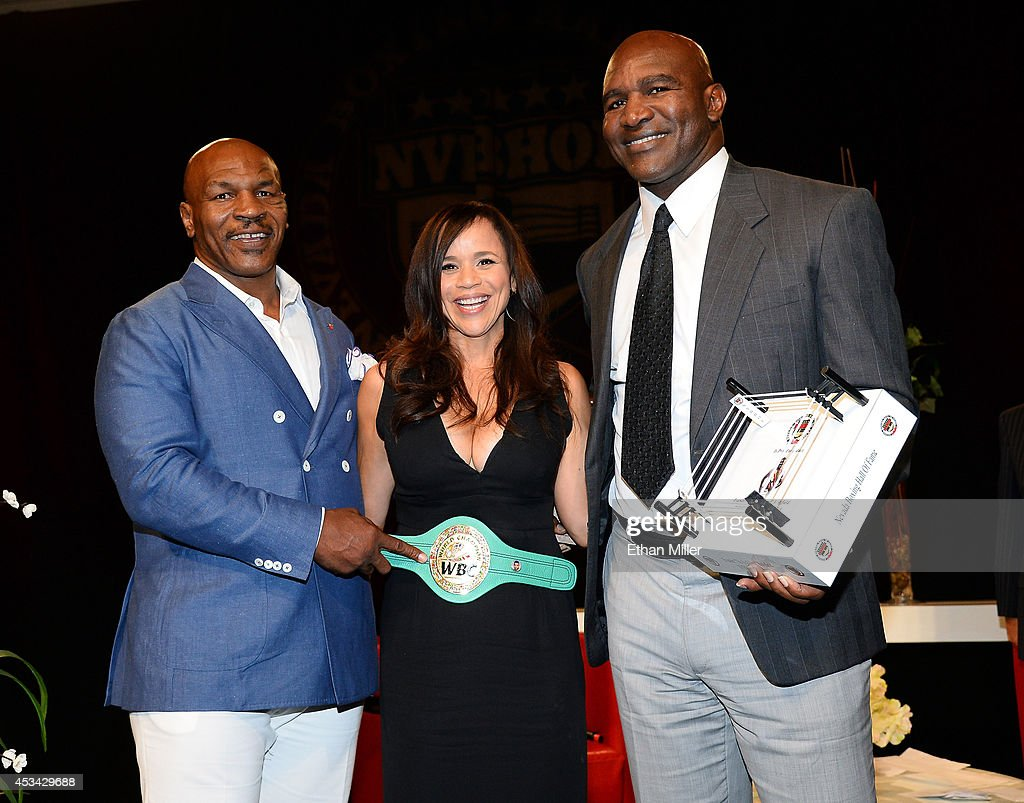 Former boxer Mike Tyson, actress and emcee Rosie Perez and former boxer Evander Holyfield pose onstage after Tyson inducted Holyfield into the Nevada Boxing Hall of Fame at the second annual induction gala at the New Tropicana Las Vegas on August 9, 2014 in Las Vegas, Nevada.