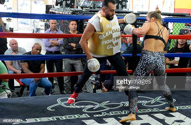 Former boxer Mike Tyson and UFC president Dana White watch UFC Bantamweight champion Ronda Rousey as she spars with trainer Edmond Tarverdyan during...