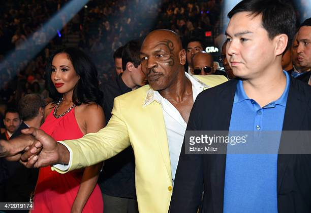 Former boxer Mike Tyson shakes hands ringside as he and his wife Lakiha 'Kiki' Tyson arrive at 'Mayweather VS Pacquiao' presented by SHOWTIME PPV And...