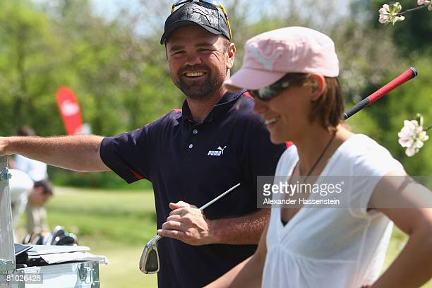 Former Boxing champ Sven Ottke smiles with soccer player Bianca Rech during the Puma meets Media Golf Event at the Golf Club Erlangen on May 8 2008...