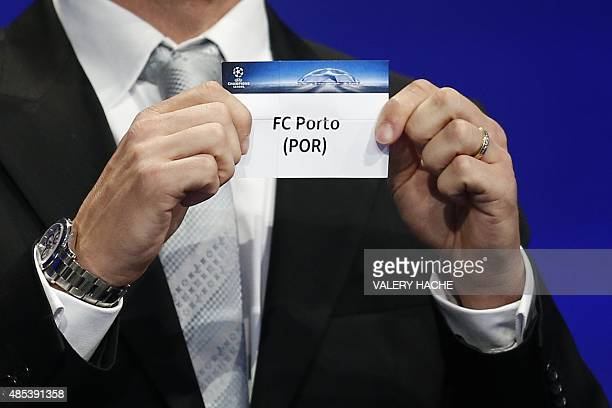 Former Brazilian football player Juliano Belletti shows the name of FC Porto football club during the UEFA Champions League Group stage draw ceremony...