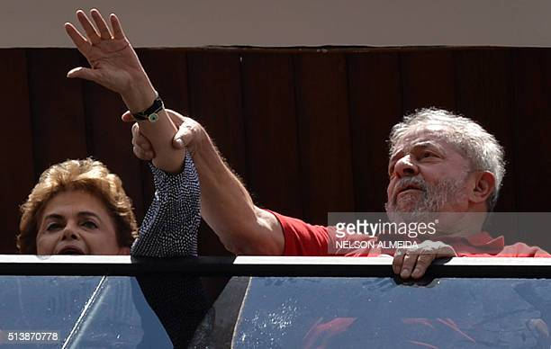 TOPSHOT Former Brazilian President Luiz Inacio Lula da Silva and current president Dilma Rousseff greet supporters gathering outside his house to...