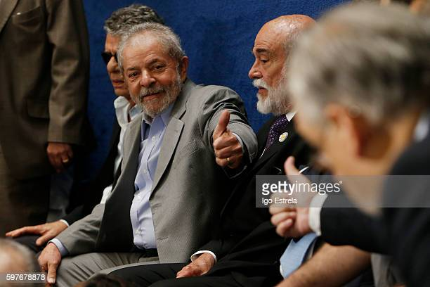 Former Brazilian President Luiz Inacio Lula da Silva gestures with a thumbs up as he attends the impeachment trial for suspended Brazilian President...