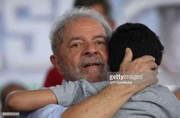 Former Brazilian President Luiz Inacio Lula da Silva hugs a boy as he meets farmers during his 'Lula for Brazil' bus tour of 20 cities in...