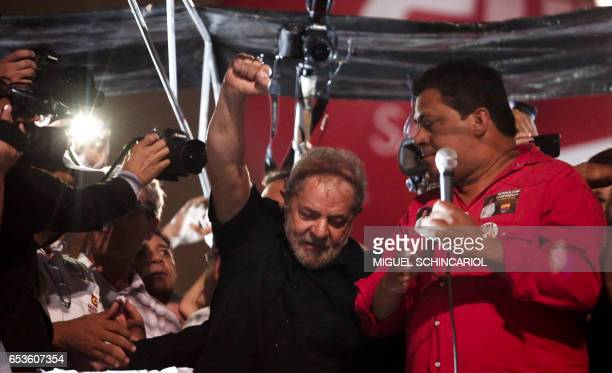 Former Brazilian President Luiz Inacio Lula da Silva rises his fist towards supporters as he takes part in a protest during a national strike against...