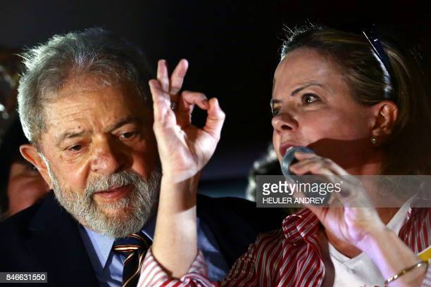 Former Brazilian president Luis Inacio Lula da Silva stands next to Senator Gleisi Hoffmann as she addresses supporters of the expresident during a...