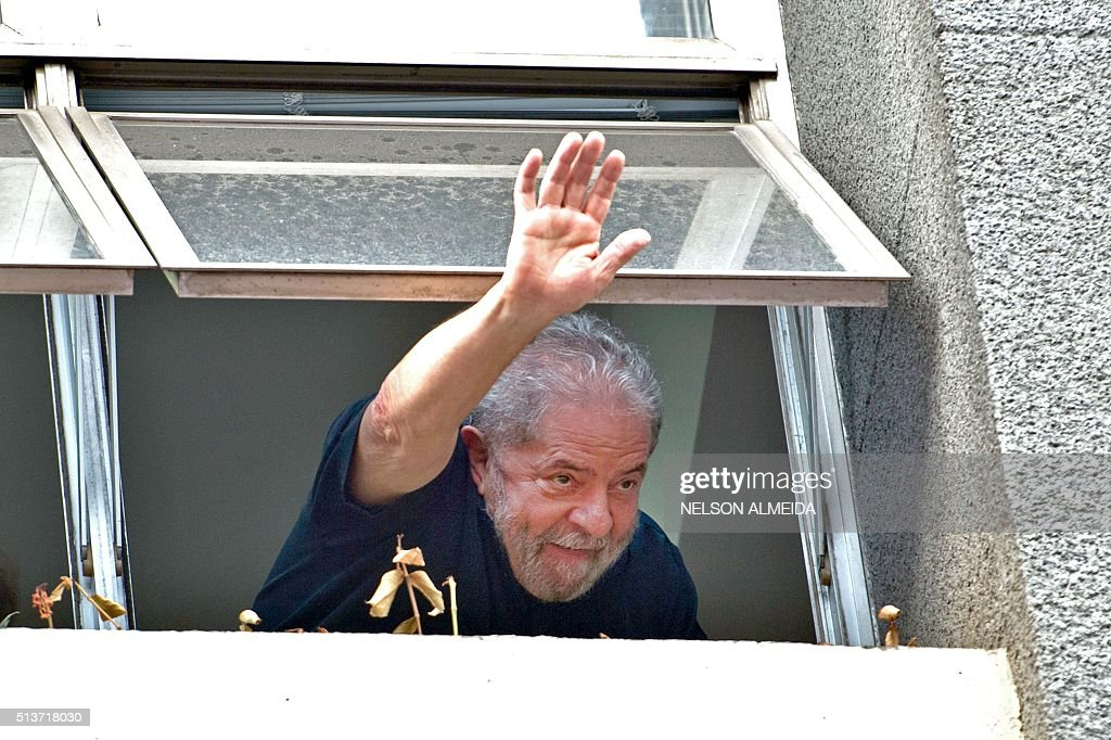 Former Brazilian President <a gi-track='captionPersonalityLinkClicked' href=/galleries/search?phrase=Luiz+Inacio+Lula+da+Silva&family=editorial&specificpeople=211609 ng-click='$event.stopPropagation()'>Luiz Inacio Lula da Silva</a> waves at supporters from a window of the Workers Party (PT) state headquarters in Sao Paulo, Brazil, on March 4, 2016. Police searched the home of Brazil's powerful ex-president <a gi-track='captionPersonalityLinkClicked' href=/galleries/search?phrase=Luiz+Inacio+Lula+da+Silva&family=editorial&specificpeople=211609 ng-click='$event.stopPropagation()'>Luiz Inacio Lula da Silva</a> and detained him for questioning Friday in a probe into a huge corruption scheme. The detention of Lula da Silva for questioning and the search of his home by officers probing a corruption network amounts to an attack on the rule of law, his spokesman said Friday.