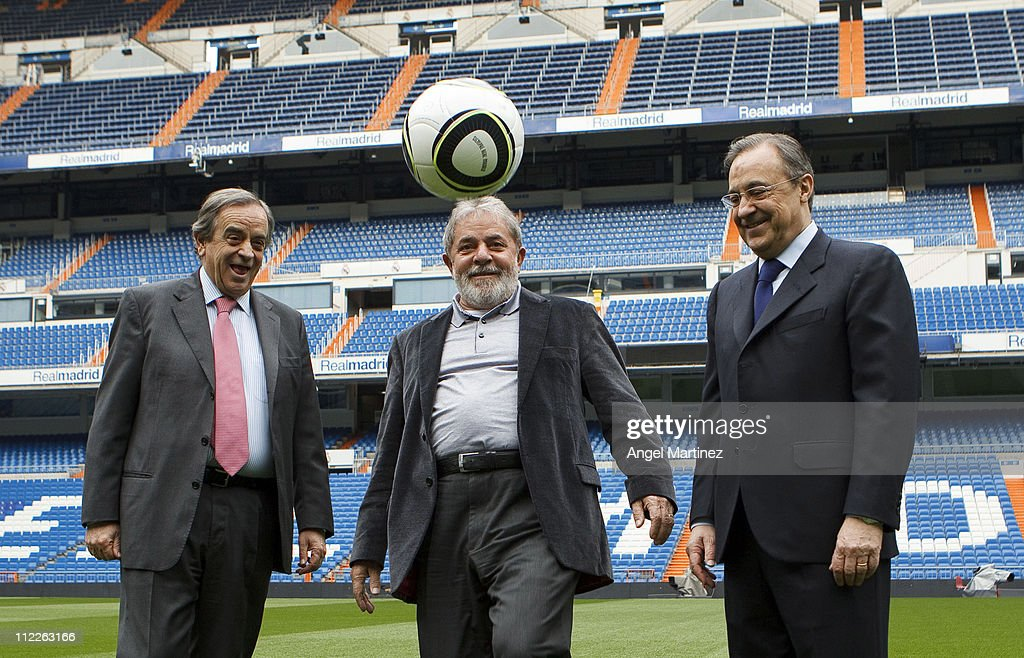 Former Brazilian President Lula da Silva (C) touches the ball beside President Florentino Perez (R) of Real Madrid during a visit to the Estadio Santiago Bernabeu on April 16, 2011 in Madrid, Spain.