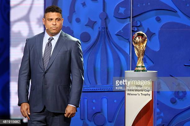 Former Brazilian striker Ronaldo stands next to the World Cup trophy during the preliminary draw for the South American Football Confederation zone...