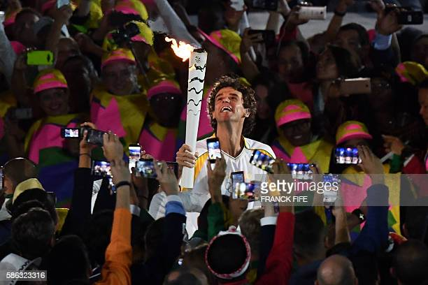 TOPSHOT Former Brazilian tennis player Gustavo Kuerten carries the Olympic torch during the opening ceremony of the Rio 2016 Olympic Games at...
