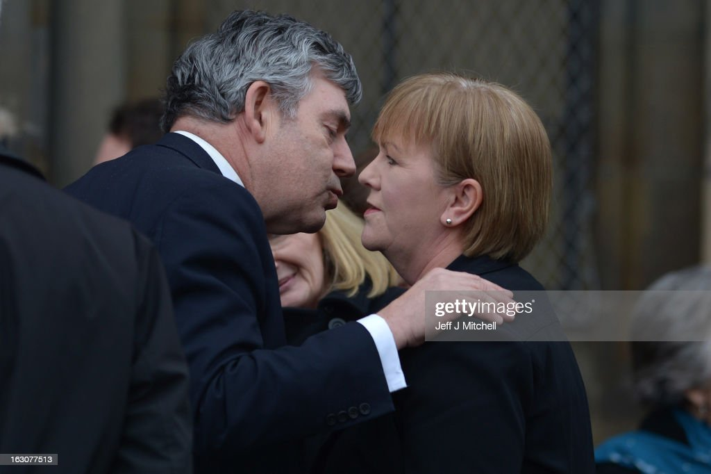 Former British Prime Minister <a gi-track='captionPersonalityLinkClicked' href=/galleries/search?phrase=Gordon+Brown&family=editorial&specificpeople=158992 ng-click='$event.stopPropagation()'>Gordon Brown</a> kisses Scottish Labour Leader Johann Lamont as they attend the memorial service of former Scottish Secretary and European Commissioner Bruce Millan at Govan Parish Church on March 4, 2013 in Glasgow, Scotland. Bruce Millan died on February 21, aged 85, after having been recently diagnosed with cancer.