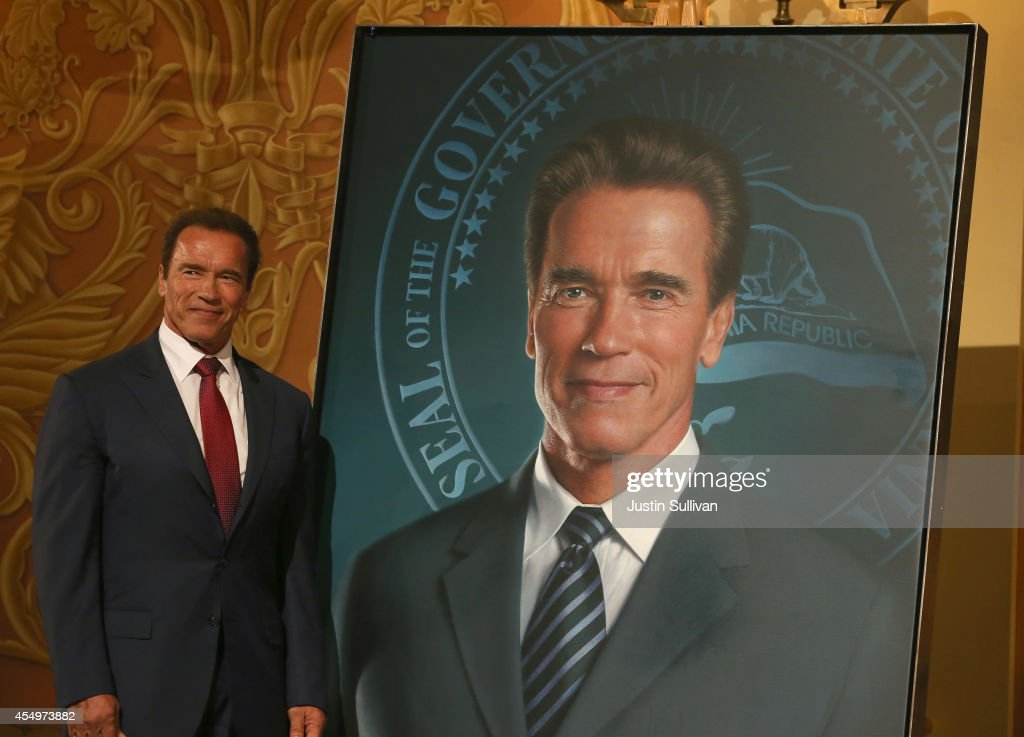 Former California Gov Arnold Schwarzenegger poses next to his gubernatorial portrait at the unveiling in the Rotunda of the State Capitol September 8...