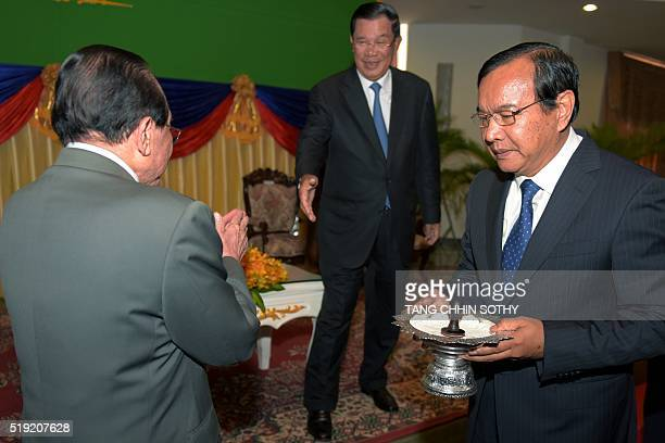 Former Cambodian Foreign Minister Hor Namhong prepares to shake hands with Prime Minister Hun Sen as new Foreign Minister Prak Sokhon holds a...