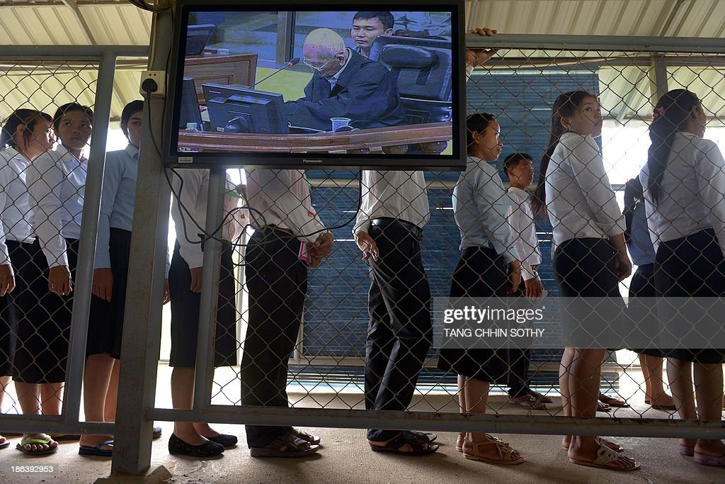 Former Cambodian Khmer Rouge leader 'Brother Number Two' Nuon Chea is seen on a livefeed video as people line up to attend the trial of former Khmer Rouge leaders at the Extraordinary Chamber in the Courts of Cambodia (ECCC) in Phnom Penh on October 31, 2013. Two former Khmer Rouge leaders make their closing statements on October 31 in the landmark trial against surviving members of the murderous regime at Cambodia's UN-backed war crimes court.