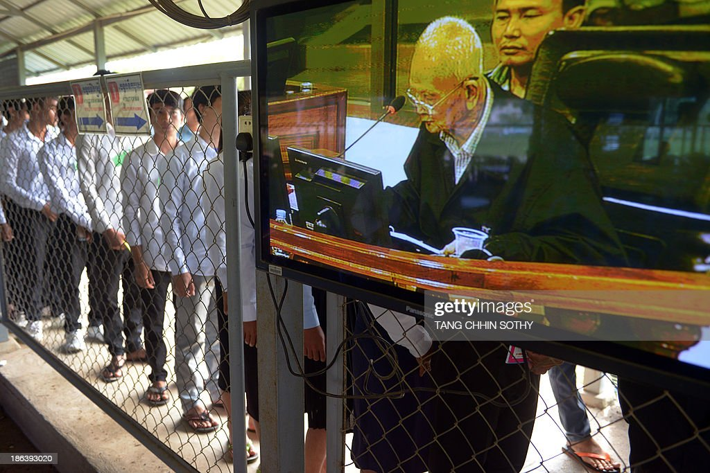 Former Cambodian Khmer Rouge leader 'Brother Number Two' Nuon Chea (R) is seen on a livefeed video as people (L) line up to attend the trial of former Khmer Rouge leaders at the Extraordinary Chamber in the Courts of Cambodia (ECCC) in Phnom Penh on October 31, 2013. Two former Khmer Rouge leaders make their closing statements on October 31 in the landmark trial against surviving members of the murderous regime at Cambodia's UN-backed war crimes court.