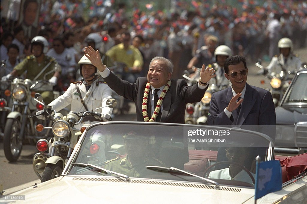 Former Cambodian King, Prince Norodom Sihanouk (L) and Cambodian Prime Minister Hun Sen wave to audience during the welcome parade to celebrate Sihanouk's return to Cambodia for the first time in 13 years, on November 14, 1991 in Phnom Penh, Cambodia.