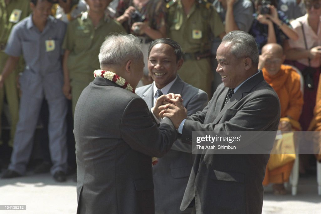 Former Cambodian King, Prince Norodom Sihanouk (L) is welcomed by Chairman of the State Council of Cambodia Heng Samrin (R) and President of the National Assembly Chea Sim (C) upon arrival at Pochentong International Airport on November 14, 1991 in Phnom Penh, Cambodia. Prince Sihanouk returns to Cambodia for the first time in almost 13 years.