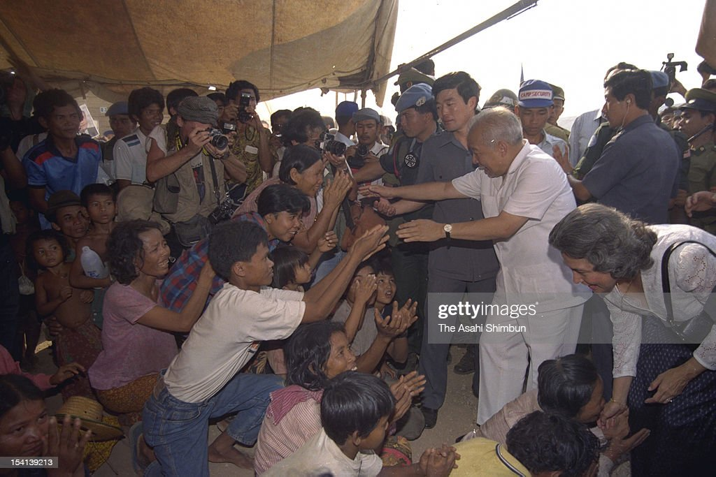 Former Cambodian King, Prince <a gi-track='captionPersonalityLinkClicked' href=/galleries/search?phrase=Norodom+Sihanouk&family=editorial&specificpeople=210861 ng-click='$event.stopPropagation()'>Norodom Sihanouk</a> (2R) shakes hands with refugees having escaped from Pol Pot group, or Khmer Rouge, returning from Thailand on March 30, 1992 in Sisophon, Cambodia.