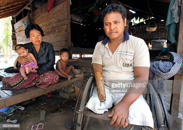 A former Cambodian soldier landmine victimwho lost both legs one arm and one of his eyes during the war pictured with his wife and his children at...