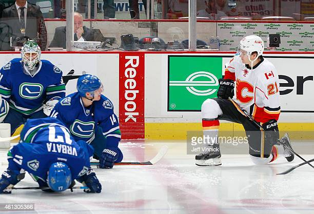 Former Canuck Mason Raymond of the Calgary Flames chats with Alexandre Burrows of the Vancouver Canucks during warmup before their NHL game against...