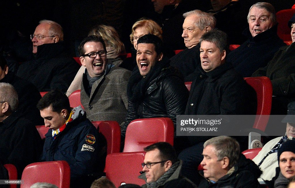 Former captain of the German national team Michael Ballack (C) laughs as he follows the game on the tribune during the Germany vs Kazakhstan FIFA 2014 World Cup qualifying football match in Nuremberg, on March 26, 2013. AFP PHOTO / PATRIK STOLLARZ