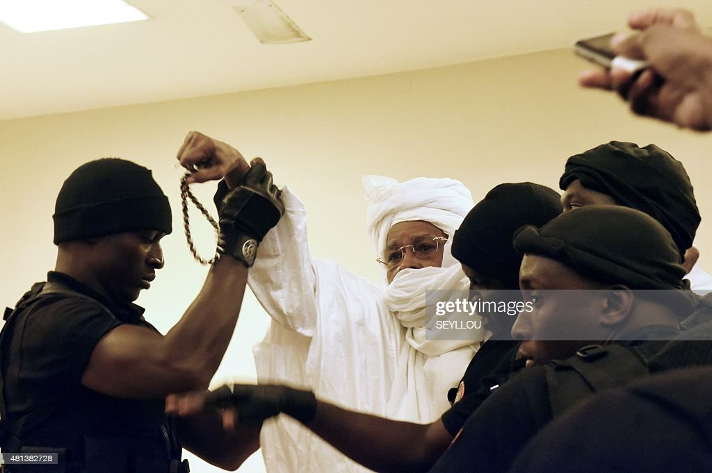 Former Chadian dictator <a gi-track='captionPersonalityLinkClicked' href=/galleries/search?phrase=Hissene+Habre&family=editorial&specificpeople=1043137 ng-click='$event.stopPropagation()'>Hissene Habre</a> (C) is escorted by prison guards into the courtroom for the first proceedings of his trial by the Extraordinary African Chambers in Dakar on July 20, 2015. More than a quarter-century after his blood-soaked reign came to an end, former Chadian dictator <a gi-track='captionPersonalityLinkClicked' href=/galleries/search?phrase=Hissene+Habre&family=editorial&specificpeople=1043137 ng-click='$event.stopPropagation()'>Hissene Habre</a> went on trial in a Senegalese court on July 20 in what is seen as a test case for African justice.
