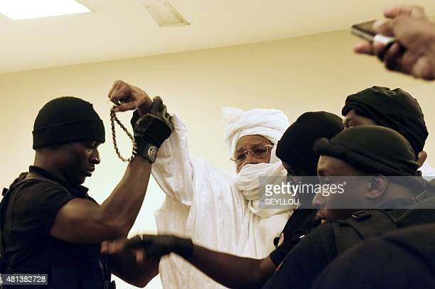 Former Chadian dictator Hissene Habre is escorted by prison guards into the courtroom for the first proceedings of his trial by the Extraordinary...