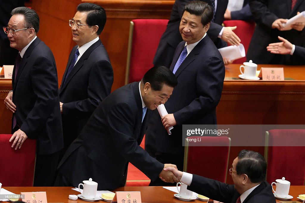 Former chairman of the Chinese People's Political Consultative Conference Jia Qinglin shakes hands with the newlyappointed chairman of the CPPCC Yu...