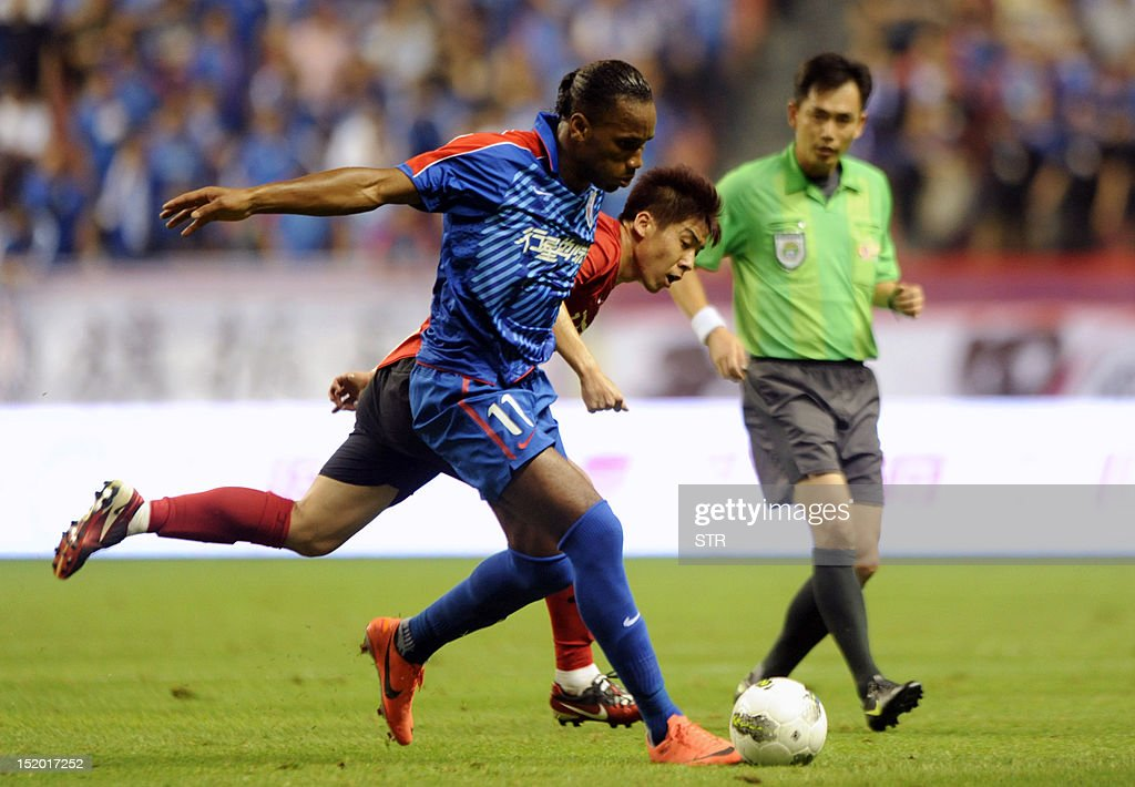 Former Chelsea star Didier Drogba (L) of Shanghai Shenhua fields the ball, before his team beat Liaoning Whowin 3-0, in the Chinese Super League (CSL) match in Shanghai on September 15, 2012. The futures of Drogba and team-mate Anelka were put in doubt last month when a Shanghai newspaper claimed that eccentric owner Zhu Jun, who pays the huge wages of the star pair, had threatened to withdraw funding. AFP PHOTO