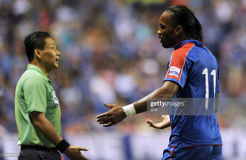Former Chelsea star Didier Drogba (R) of Shanghai Shenhua speaks with the referee, before his team beat Liaoning Whowin 3-0, in the Chinese Super League (CSL) match in Shanghai on September 15, 2012. The futures of Drogba and team-mate Anelka were put in doubt last month when a Shanghai newspaper claimed that eccentric owner Zhu Jun, who pays the huge wages of the star pair, had threatened to withdraw funding.