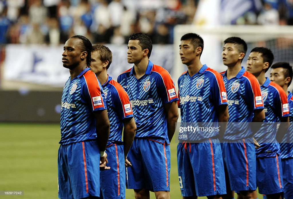 Former Chelsea star Didier Drogba (L) with his Shanghai Shenhua teammates wait for the start of the match against Liaoning Whowin which they beat 3-0 in the Chinese Super League (CSL) in Shanghai on September 15, 2012. The futures of Drogba and team-mate Anelka were put in doubt last month when a Shanghai newspaper claimed that eccentric owner Zhu Jun, who pays the huge wages of the star pair, had threatened to withdraw funding. AFP PHOTO