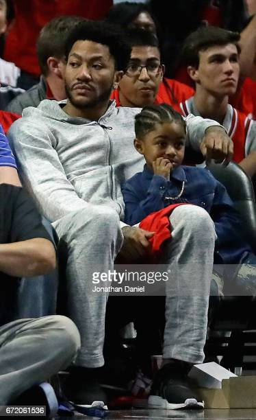 Former Chicago Bulls player Derrick Rose watches with son PJ as the Bulls take on the Boston Celtics during Game Four of the Eastern Conference...