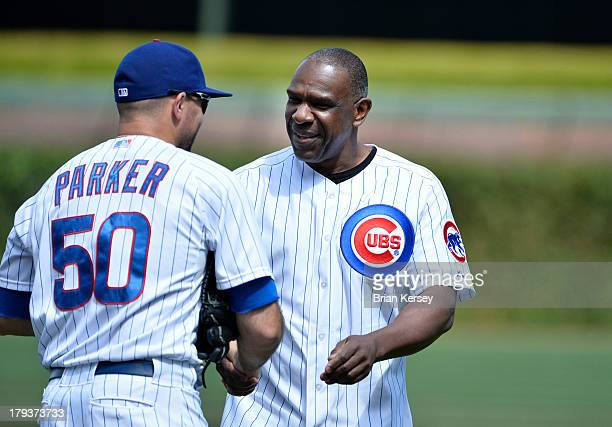 Former Chicago Cub Andre Dawson shakes hands with Blake Parker of the Chicago Cubs after throwing out a ceremonial first pitch before the game...