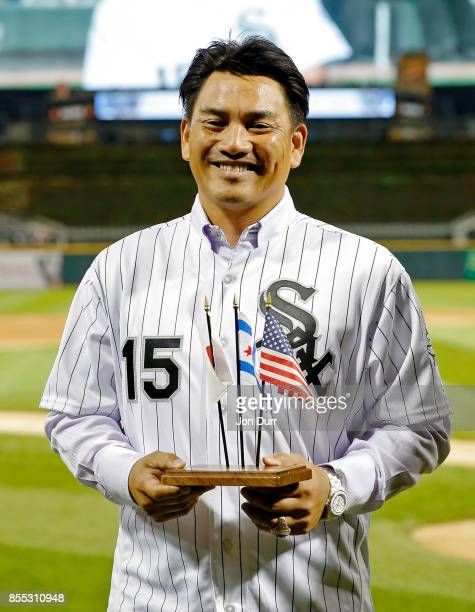 Former Chicago White Sox player Tadahito Iguchi holds miniture flags and smiles while he is honored by Naoki Ito consul general of Japan in Chicago...