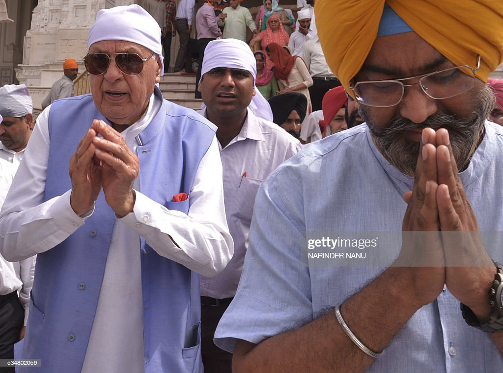 Former chief minister of the Indian state of Jammu and Kashmir and member of the main state opposition party the National Conference (NC) Farooq Abdullah, (L), gestures as he arrives for a visit to the Golden Temple in Amritsar on May 28, 2016. / AFP / NARINDER