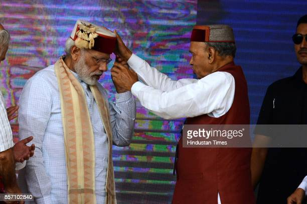 Former Chief Minister Prem Kumar Dhumal helps Prime Minister Narendra Modi to set the mehroon colour cap during a BJP Abhar Rally at Luhnu ground on...