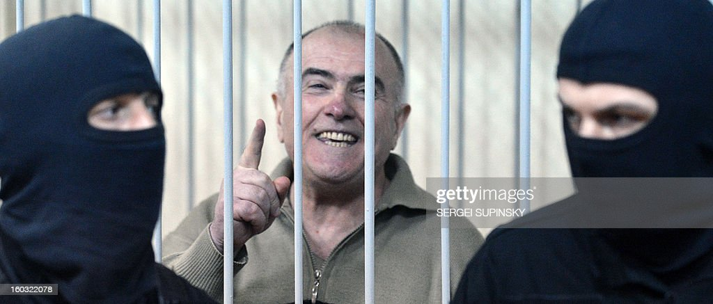 Former chief of the external surveillance department of the Ukrainian Interior Ministry Oleksiy Pukach smiles as says that the former president Leonid Kuchma and the former speaker Volodymyr Lytvyn must to be together with him in the cage, after the verdict reading of his trial for the murder of opposition journalist Georgy Gongadze in 2000, on January 29, 2013 at Kiev district court. Ukraine jails ex-top official for life over journalist murder .
