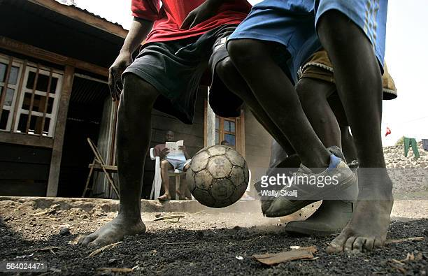 Former child soldiers play soccer some barefoot on a bed of broken lava rock at a transit center in Goma Congo Over 35000 childrenn were forced to...