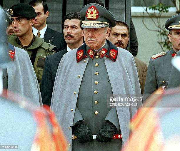 Former Chilean leader and current Commander of the Chilean Armed Forces Gen Augusto Pinochet listens to a military band playing before his residence...