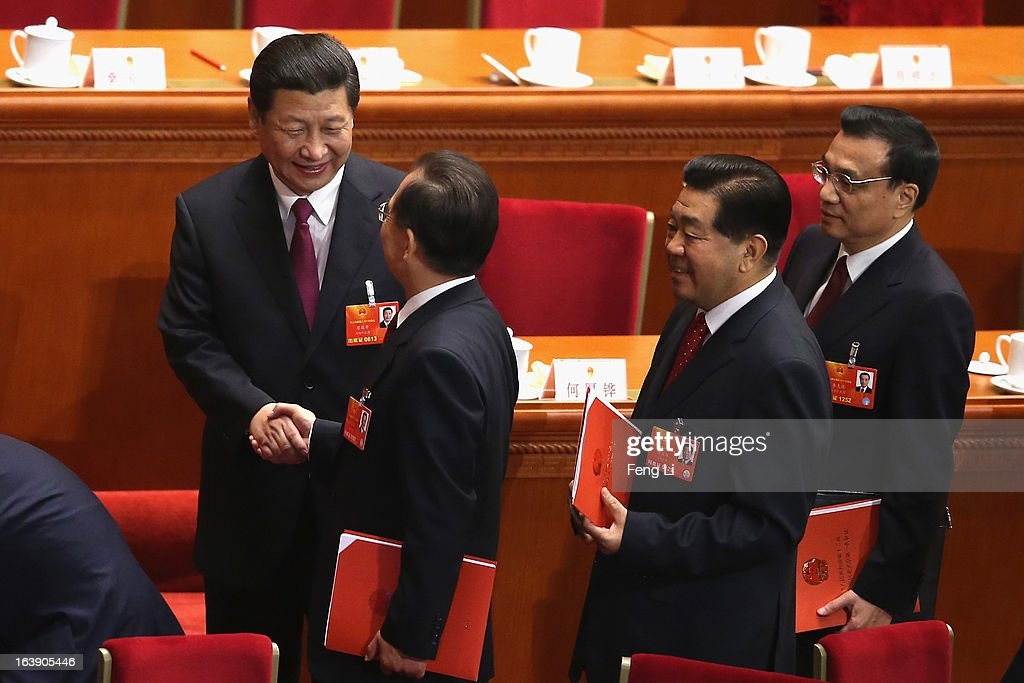 Former Chinese Premier Wen Jiabao shakes hands with newly-elected Chinese President Xi Jinping (L) as Chinese Premier Li Keqiang (R) looks on after the closing session of the National People's Congress (NPC) at the Great Hall of the People on March 17, 2013 in Beijing, China. China's newly-elected president Xi Jinping pledged Sunday to resolutely fight against corruption and other misconduct in all manifestations.