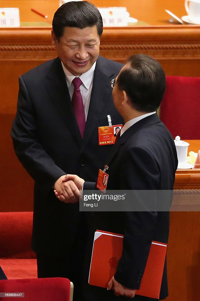 Former Chinese premier Wen Jiabao (R) shakes hands with newly-elected Chinese President Xi Jinping (L) after the closing session of the National People's Congress (NPC) at the Great Hall of the People on March 17, 2013 in Beijing, China. China's newly-elected president Xi Jinping pledged Sunday to resolutely fight against corruption and other misconduct in all manifestations.