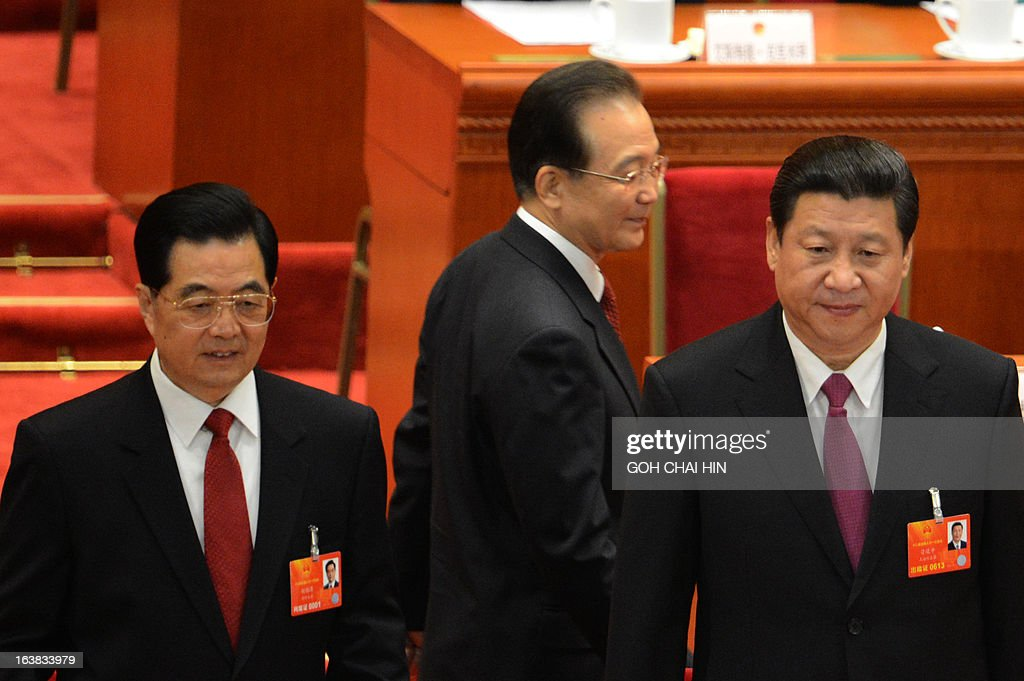 Former Chinese premier Wen Jiabao (C) walks past former Chinese president Hu Jintao (R) and the newly-elected President Xi Jinping at the closing session of the National People's Congress (NPC) at the Great Hall of the People in Beijing on March 17, 2013. China's new Premier Li Keqiang steps into the media spotlight on March 17 for a rare press conference, as the annual meeting of the country's rubber-stamp parliament closes. AFP PHOTO/GOH CHAI HIN