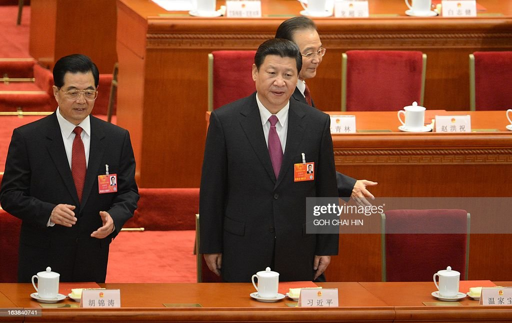 Former Chinese premier Wen Jiabao (R) walks past former Chinese president Hu Jintao (L) and the newly-elected Chinese President Xi Jinping at the closing session of the National People's Congress (NPC) at the Great Hall of the People in Beijing on March 17, 2013. China's new Premier Li Keqiang steps into the media spotlight on March 17 for a rare press conference, as the annual meeting of the country's rubber-stamp parliament closes. AFP PHOTO/GOH CHAI HIN