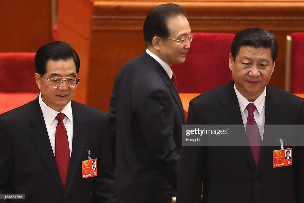 Former Chinese premier Wen Jiabao (C) walks past former Chinese president Hu Jintao (L) and the newly-elected President Xi Jinping (R) at the closing session of the National People's Congress (NPC) at the Great Hall of the People on March 17, 2013 in Beijing, China. China's newly-elected president Xi Jinping pledged Sunday to resolutely fight against corruption and other misconduct in all manifestations.