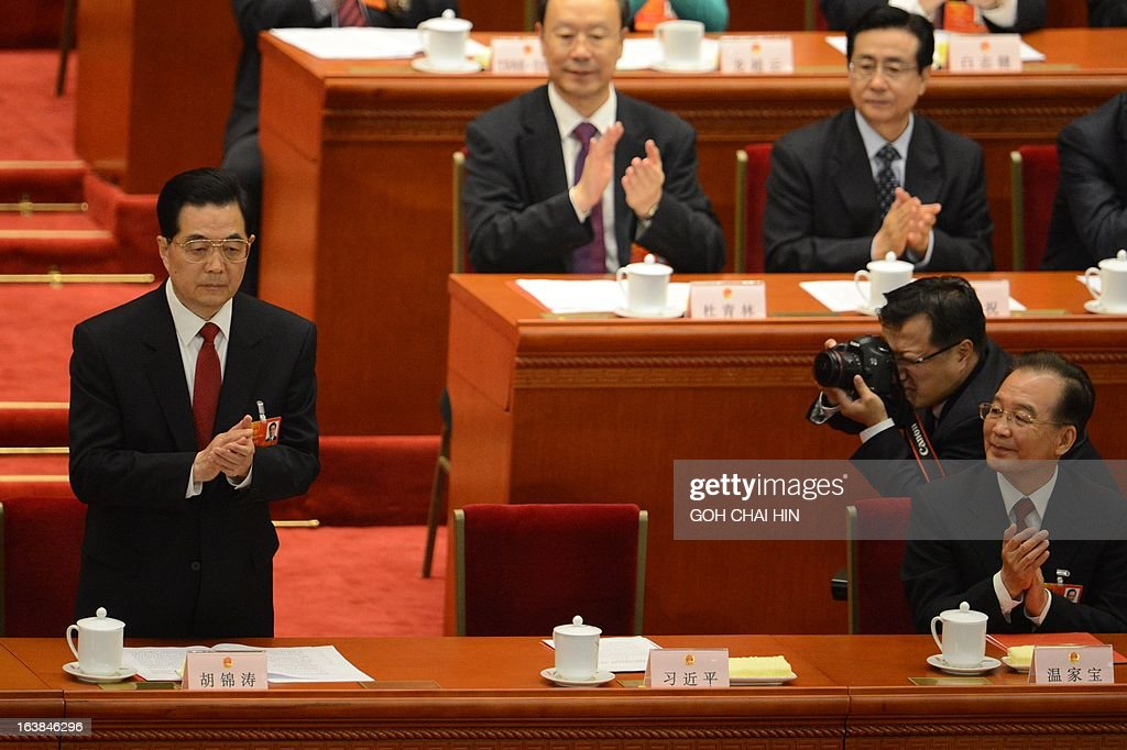 Former Chinese president Hu Jintao (L) bows to delegates as President Xi Jinping thanks him during the latter's maiden speech at the closing session of the National People's Congress (NPC) at the Great Hall of the People in Beijing on March 17, 2013. Xi said he would fight for a 'great renaissance of the Chinese nation', in his first speech as head of state of the world's most populous country.