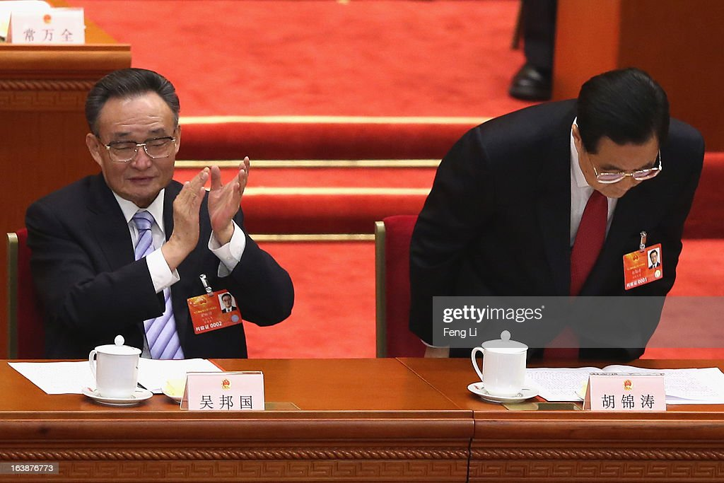 Former Chinese president Hu Jintao (R) bows to delegates as President Xi Jinping thanks him during the latter's maiden speech at the closing session of the National People's Congress (NPC) at the Great Hall of the People on March 17, 2013 in Beijing, China. China's newly-elected president Xi Jinping pledged Sunday to resolutely fight against corruption and other misconduct in all manifestations.