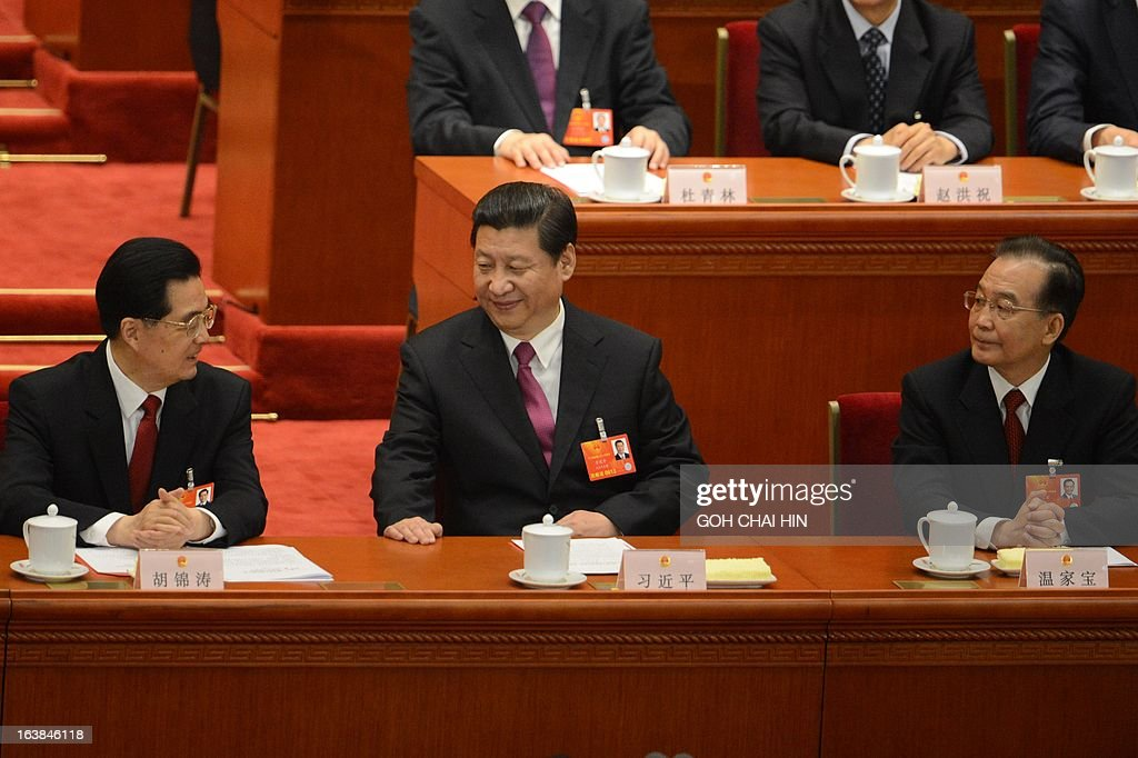 Former Chinese president Hu Jintao (L) speaks to newly-elected Chinese President Xi Jinping (C) while former premier Wen Jiabao (R) listens, at the closing session of the National People's Congress (NPC) at the Great Hall of the People in Beijing on March 17, 2013. Xi said he would fight for a 'great renaissance of the Chinese nation', in his first speech as head of state of the world's most populous country. AFP PHOTO/GOH CHAI HIN