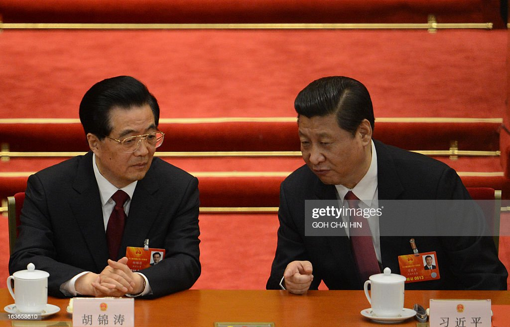 Former Chinese President Hu Jintao (L) talks to newly-elected President Xi Jinping after the election of the new president of China during the 12th National People's Congress (NPC) in the Great Hall of the People in Beijing on March 14, 2013. Chinese Communist Party leader Xi Jinping was named president of the world's most populous country after a vote at its parliamentary meeting in Beijing.