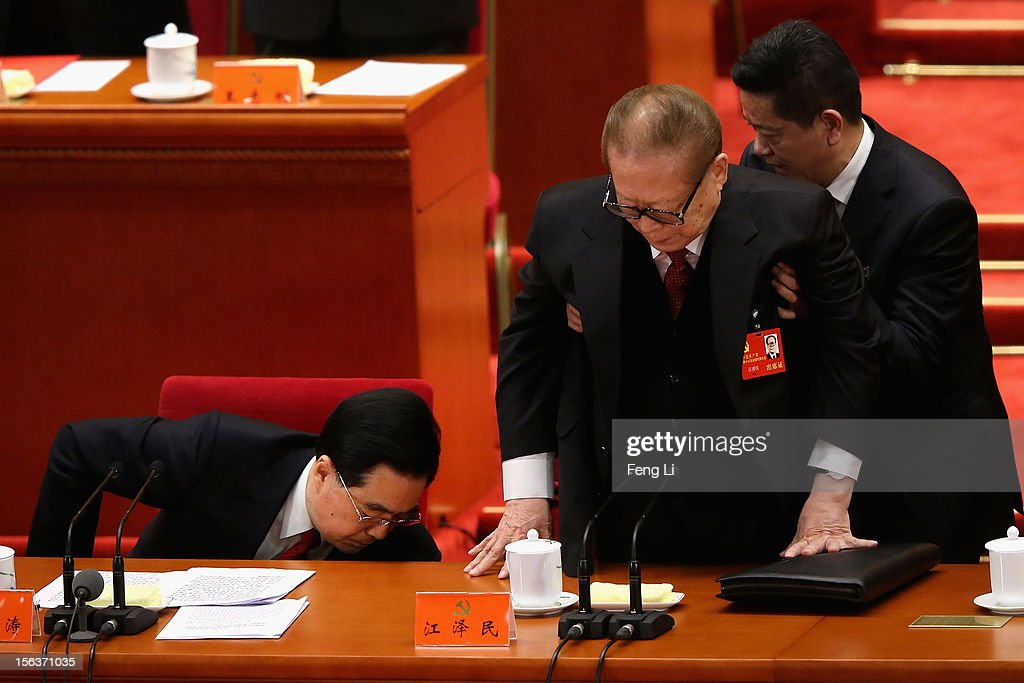 Former Chinese president Jiang Zemin gets helped standing up as President Hu Jintao goes down to pick up a document during the closing session of the...