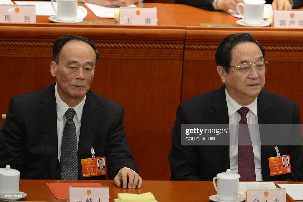 Former Chinese vice president Wang Qishan (L) and Shanghai Party Chief Yu Zhengsheng present at the closing session of the National People's Congress (NPC) at the Great Hall of the People in Beijing on March 17, 2013. President Xi Jinping said he would fight for a 'great renaissance of the Chinese nation', in his first speech as head of state of the world's most populous country.